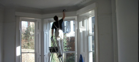 Painter Painting the Exterior of a Home